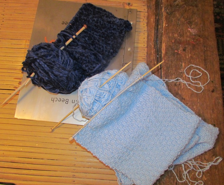 Light blue Scarf in alternating Knit 2, Purl 2 Pattern with Navy Blue Chenille infinity scarf in the background.